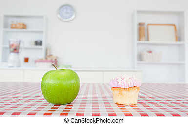 An apple and a cupcake on a tablecloth in a kitchen