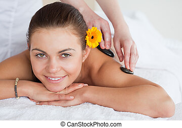 Smiling woman enjoying a hot stone massage with a flower on...