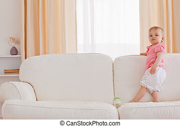 Baby standing on a sofa in the living room