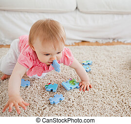 Lovely blond baby playing with puzzle pieces on a carpet in...