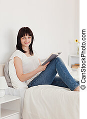 Good looking brunette woman reading a book while sitting on a bed in her appartment