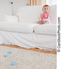 Cute blond baby playing with puzzle pieces while sitting on a sofa in the living room