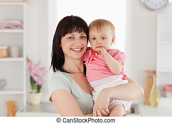 Beautiful woman holding her baby in her arms while standing...