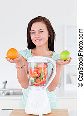 Happy woman with a blender and fruits