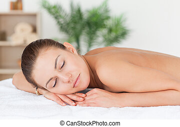 Close up of a woman lying on her belly closing her eyes
