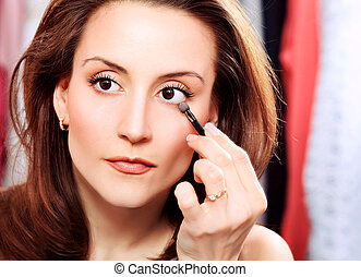 eyeshadow - Young beautiful woman making up at home.