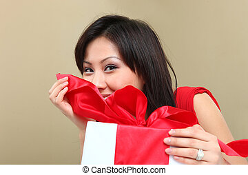 Woman Holding a Wrapped Gift Package - Asian Woman Holding a...