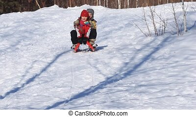 Winter entertainment - A boy and a girl driving in a sled...