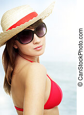 Young woman wearing sunglasses on a light background