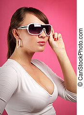 Young woman wearing sunglasses on pink background