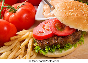 hamburger with fries and vegetables