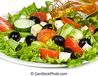 vegetable salad with olive oil pouring from a bottle on...