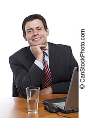 Young man in suit sitting happy at desk with laptop