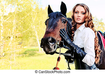 equitation - Beautiful young woman with a horse outdoor.