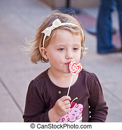 Lollypop - Cute little European toddler girl having fun...