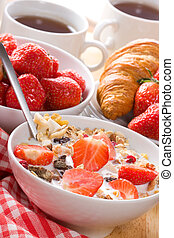 Breakfast with cereals in bowl with strawberries