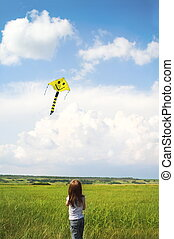 Little girl with flying a kite