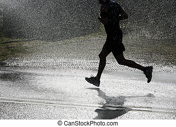 Running in the heat. - The runner passing a jet of water for...