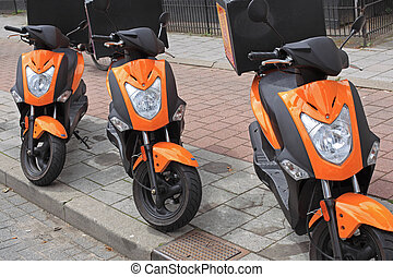 Three orange pizza delivery mopeds alongside a street