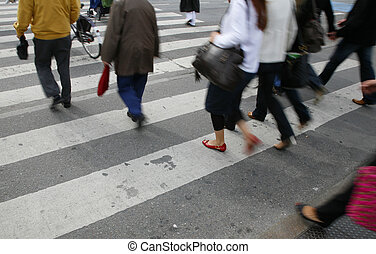 Rush hour in an urban zebra crossing. Focus on red shoe....