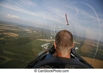 Glider pilot in the air with his plane gliding away in the...