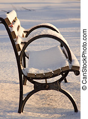 Snow covered park bench - Snow covered park bench at early...