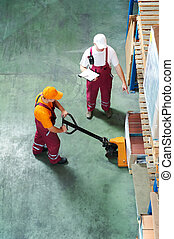 Warehouse workers with fork pallet truck stacker - Two...