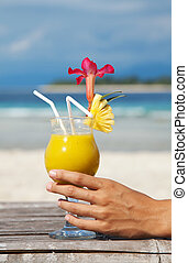 Cocktail on tropical beach - Woman holding a cocktail on a...