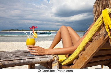 Woman with a cocktail on beach - Woman enjoying a cocktail...