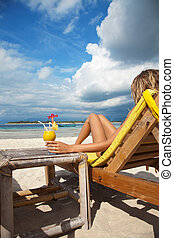 Woman with a cocktail on beach - Woman sitting on deckchair...