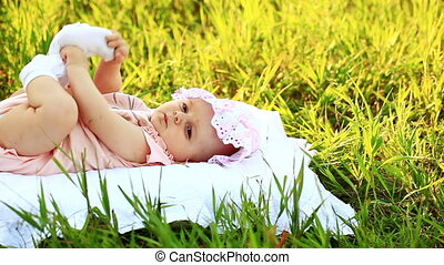 Baby lying on the grass - Child outdoors