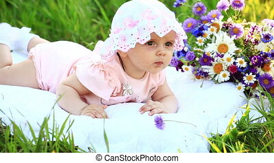 Baby lying on a pillow in meadow