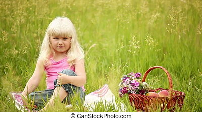 Blonde girl sitting on the grass
