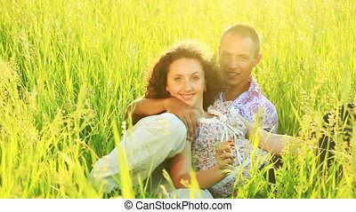 Love couple lies in the tall grass