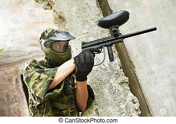 paintball player under cover - paintball sport player in...