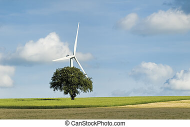 green power - a tree with a wind turbine in the background