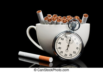 cup full of cigarettes and stopwatch isolated on a black...