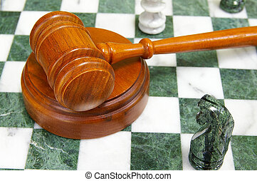 Legal gavel on a chess board with game pieces