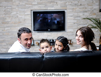 family wathching flat tv at modern home indoor - happy young...