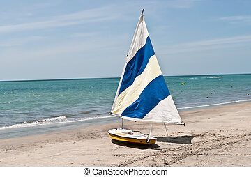 Sail boat and the ocean - Small sail boat on a sandy beach