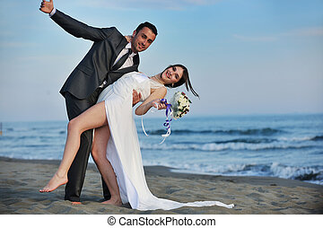 romantic beach wedding at sunset - happy just married young...