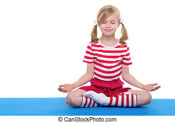 girl with eyes closed practicing yoga on blue rug