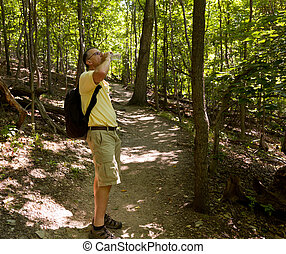 Senior man hiking in forest with backpack - Senior male...