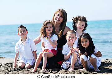 group portrait of childrens with teacher on beach - group...