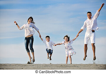 family on beach showing home sign - happy young family have...