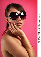 Young woman wearing sunglasses on red background