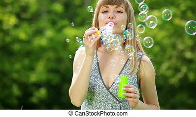 Beautiful girl blow bubbles - Family outdoors