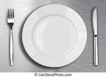 Knife, white plate and fork on metal background