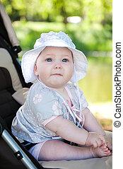 Baby in stroller - Cute baby in hat is sitting in stroller...