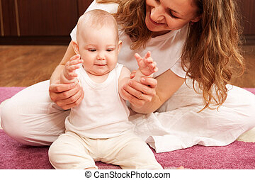 Mother playing with baby - Young mother is playing with her...